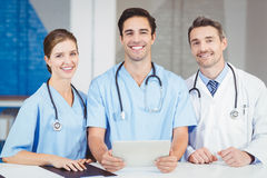 Portrait of smiling doctor and colleagues holding digital tablet Royalty Free Stock Photos