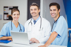 Portrait of smiling doctor and colleagues with laptop Stock Photography