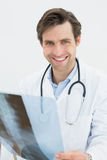 Portrait of a smiling doctor examining spine xray Stock Photo