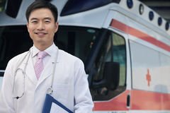 Portrait of smiling doctor holding clipboard in front of an ambulance Stock Photography