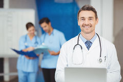 Portrait of smiling doctor with laptop and colleagues standing Stock Photography