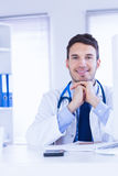 Portrait of smiling doctor looking at camera with hands folded Royalty Free Stock Image