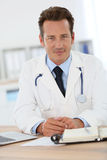Portrait of smiling doctor at medical office Stock Photos