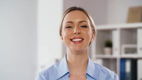 Portrait of smiling doctor or nurse at hospital. Medicine, healthcare and people concept - portrait of happy smiling female doctor or nurse at hospital stock footage