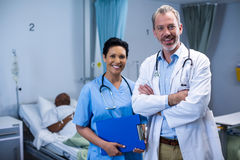 Portrait of smiling doctor and nurse in ward. Of hospital Royalty Free Stock Images
