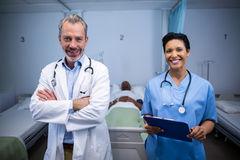 Portrait of smiling doctor and nurse in ward. Of hospital Royalty Free Stock Photography