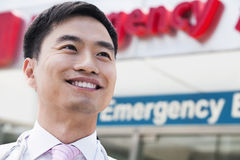 Portrait of smiling doctor outside of the hospital, emergency room sign in the background, Close-Up Stock Photo