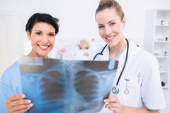 Portrait of a smiling doctor and surgeon examining xray Royalty Free Stock Images