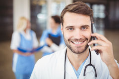 Portrait of smiling doctor talking on mobile phone Stock Photo