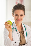 Portrait of smiling doctor woman with apple Royalty Free Stock Images