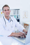Portrait of smiling doctor working with laptop Royalty Free Stock Photo