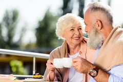 Portrait of smiling elderly couple with cups of coffee looking. At each other royalty free stock photos