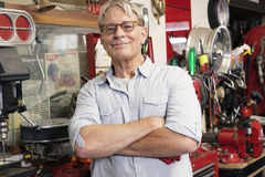 Portrait of smiling elderly man with arms crossed in workshop Royalty Free Stock Photos