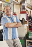 Portrait of smiling elderly man in automobile workshop Stock Photography