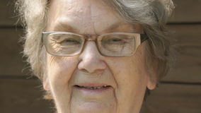 Portrait of smiling elderly woman in glasses stock video