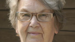 Portrait of smiling elderly woman in glasses stock footage
