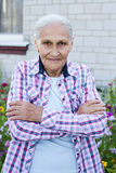 Portrait of smiling elderly woman. A photo on the hause background Stock Image