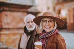 Cheerful senior lady with coffee and bearded man on blurred background stock images