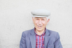 Portrait of smiling elederly man in cap Stock Photos