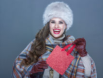 Portrait of smiling elegant woman holding small red shopping bag. Winter things. Portrait of smiling elegant woman in fur hat isolated on cold blue background Royalty Free Stock Photography