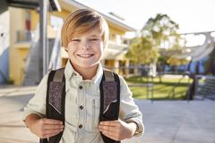 Portrait of smiling elementary school boy with his backpack stock photo