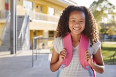 Portrait of smiling elementary school girl with her backpack royalty free stock photos