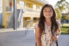 Portrait of smiling elementary school girl with her backpack royalty free stock photo