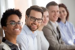 Portrait of smiling employees sit in row looking at camera. Team of multiracial millennial employees in row look at camera smiling, focus on young male worker stock photo