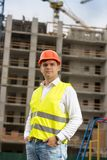 Portrait of smiling male engineer in hardhat posing against building site stock images