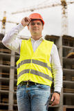 Portrait of smiling engineer in hardhat posing against working c Stock Photos