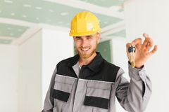 Portrait of smiling engineer in work clothes and hardhat happily. Portrait of smiling engineer in work clothes and yellow hardhat happily looking in camera Stock Image