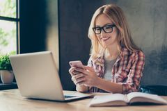 Portrait of smiling entrepreneur chatting through 5g internet, l. Ooking at her smart phone, sitting in workstation royalty free stock photography