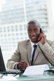 Portrait of a smiling entrepreneur making a phone call while rea Stock Photography