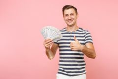 Portrait of smiling excited young man in striped t-shirt holding bundle lots of dollars, cash money, ardor gesture on. Copy space isolated on pink background stock photos
