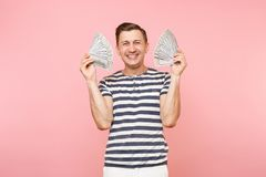Portrait of smiling excited young man in striped t-shirt holding bundle lots of dollars, cash money, ardor gesture on. Copy space isolated on pink background stock images