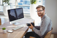 Portrait of smiling executive holding digital camera at desk Royalty Free Stock Photo