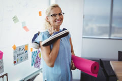Portrait of smiling executive holding exercise mat and shoes. In office Stock Photos