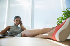 Portrait of smiling executive relaxing at desk while talking on mobile phone Stock Photos