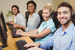 Portrait of smiling executives in call center. Portrait of smiling executives working together in call center royalty free stock photos
