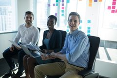 Portrait of smiling executives discussing over graph royalty free stock photo
