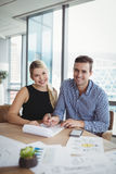 Portrait of smiling executives discussing over paper at desk Royalty Free Stock Image