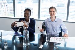 Portrait of smiling executives holding virtual reality headset. In office royalty free stock image