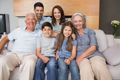 Portrait of smiling extended family on sofa in living room Stock Photo