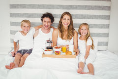 Portrait of smiling family enjoying breakfast on bed Royalty Free Stock Photos