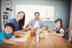 Portrait of smiling family with food on dining table Royalty Free Stock Image