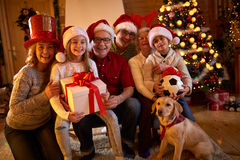 Portrait smiling family with gifts and dog at xmas Stock Image