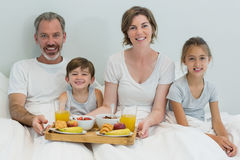 Portrait of smiling family having breakfast on bed in bedroom Royalty Free Stock Image