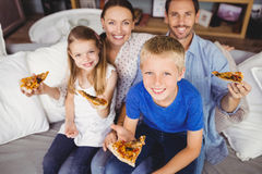 Portrait of smiling family holding pizza slices while sitting on sofa Stock Image