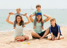 Portrait of smiling family with kids on  sand Royalty Free Stock Photo