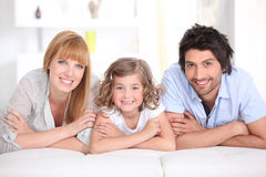 Portrait of a smiling family laid on a bed Stock Photos
